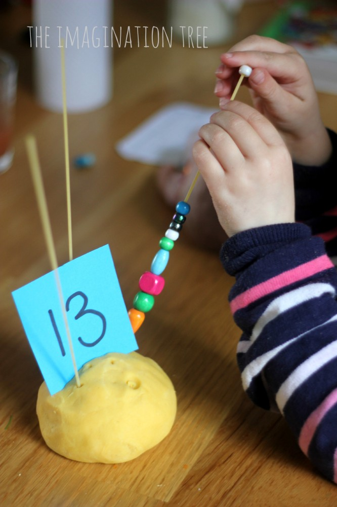 Counting beads onto spaghetti in play dough