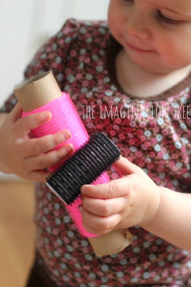 Baby playing with hair rollers