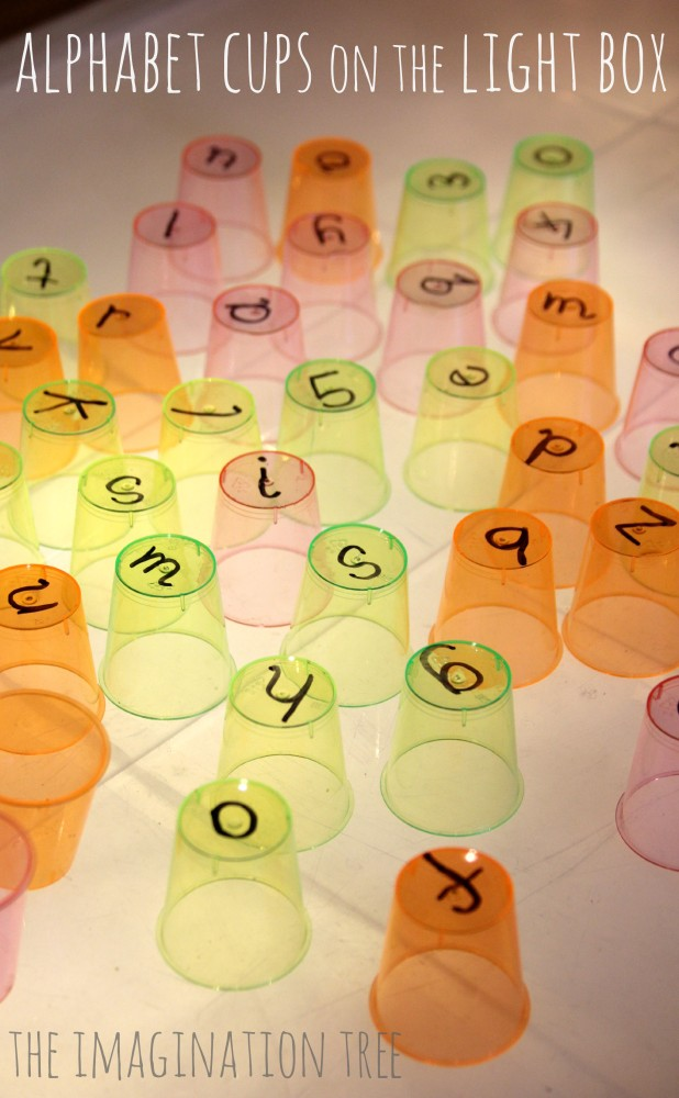 Playing with alphabet cups on the light table