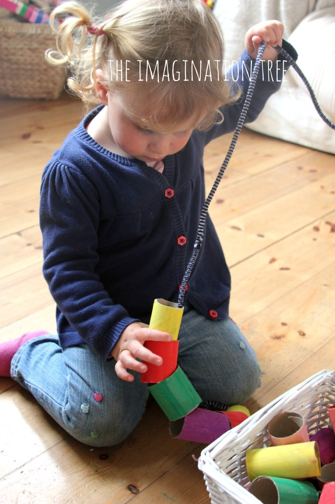 Toddler threading activity with giant cardboard beads