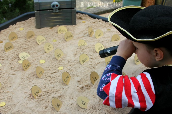 Word treasure, a fun activity where a kid dressed up like a pirate searches the sand box to find sight word doubloons to put in a black treasure chest with a skull on it.