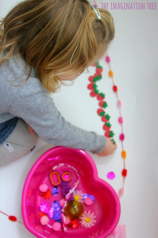 Toddler counting and sorting with a Valentine's sensory tub