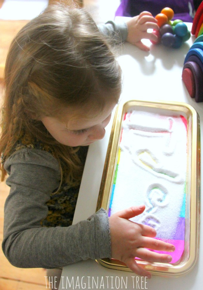 Writing in a rainbow sensory writing tray